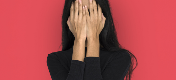 woman covering face due to acne scars, the solution is microneedling at The Skin Care Professionals in Dallas, Texas
